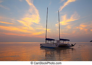 Catamaran on tropical beach at sunset