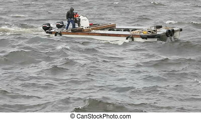 Catamaran - Two men on a motor catamaran sailing in a storm