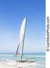 Catamaran with its colorful sails wide open on Varadero Cuban white sandy beach
