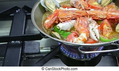 Cataplana with fresh seafood, vegetables is cooked on a gas stove, boiling very much. Horizontal video. Close-up. High quality FullHD footage
