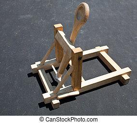 Wooden catapult toy on dark background