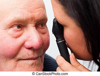 Cataracts - Optician checking elderly patient's cataracts...