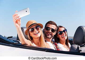 Catching a happy moment. Three young happy people enjoying road trip in their white convertible and making selfie