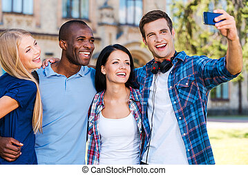 Catching a moment from student life. Four happy young people making selfie while standing close to each other outdoors
