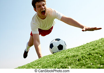 Catching ball - Image of soccer player falling down and...