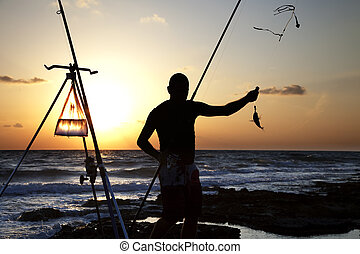 Catching the Fish - Fisherman silhouette catching a fish....