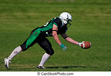 Catching the Football - A young, football player about to...