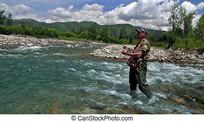 Catching trout - A fisherman catches a fish on a spinning