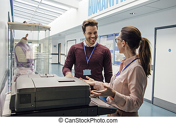 Catching Up At The Printer - Two teachers are talking while...