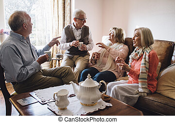 Catching Up Over Tea - Group of seniors are sitting in the...