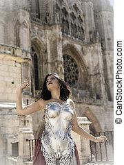 catedral, reina, en, plata, y, oro, armadura, hermoso, morena, mujer, con, largo, abrigo rojo, y, pelo marrón