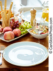 empty plate and wine glass on table with food