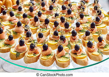 Catering of canape with olives, lemon and salmon
