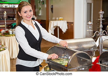 Catering service employee preparing buffet