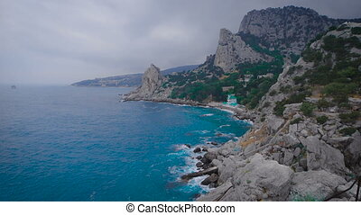 Catholic and Protestant church on the beach, at the foot of the mountain. Cloudy weather and waves