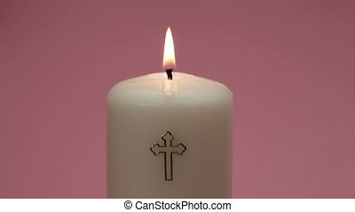 Catholic candle burning and being blown out on pink...