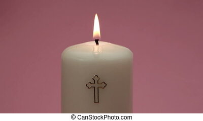 Catholic candle burning on pink background
