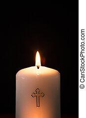 Catholic candle burning on black background