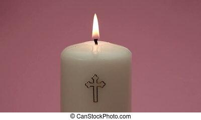 Catholic candle burning on pink background