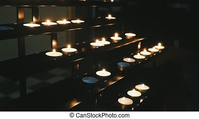 Catholic candles burning in a cathedral placed on staircase looking shelves