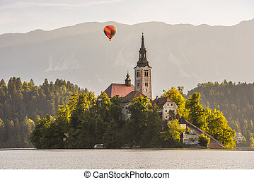 Catholic Church in Bled Lake, Slovenia with Hot Air Balloon Flying at Sunrise