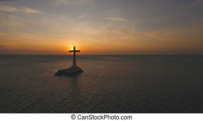 Catholic cross in the sea at sunset. - Aerial view Sunken...