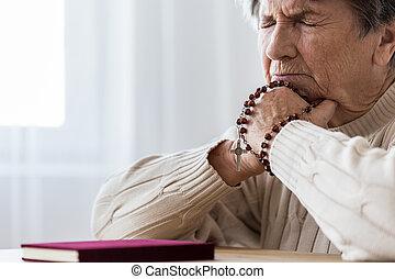 Catholic elderly woman in melancholy