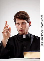 Catholic man with rosary in hand and the Bible