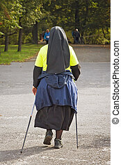 Catholic Nun in park - Nordic walking