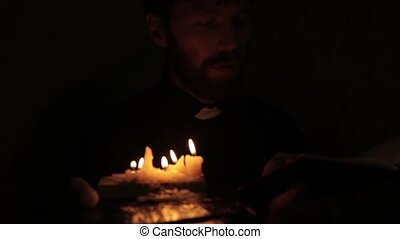 catholic pastor lights candles and reading from the holy...