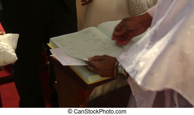 Catholic priest give book to groom