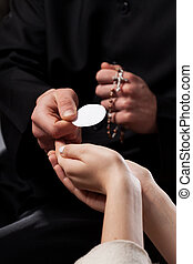 Holy Communion - Catholic priest giving beliver a Holy...