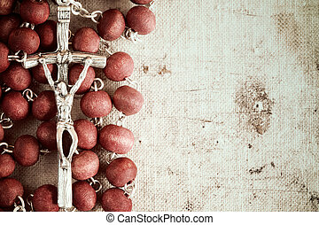 Catholic rosary on old dirty canvas background with...