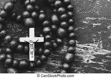 Catholic rosary prayer with a cross on old black wooden background with space for text. close-up, top view. black and white toned photo