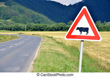 Cattle crossing traffic sign next to the empty road, close-up.