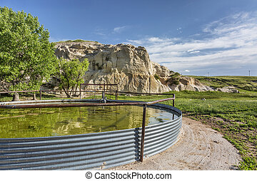 cattle water tank and rock cliff, Pawnee Grassland in ...