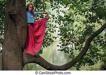 caucásico, mujer estar de pie, en, yoga, balance, utthita, hasta, padangusthasana, pose., ella, asimiento, trank, de, árbol