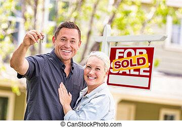 caucásico, pareja, delante de, vendido, signo bienes raíces, y, casa, con, llaves