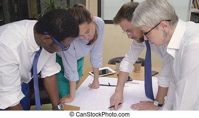 Caucasian, african, asian colleagues brainstorming apartment house blueprint.