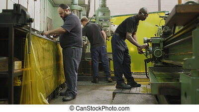 Caucasian and African American male factory worker standing ...