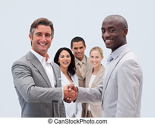 Caucasian and Afro-American businessmen shaking hands with...