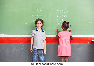 Caucasian and afroamerican schoolkids learning math on chalkboard
