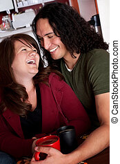 Caucasian and Native American couple embracing at a cafe
