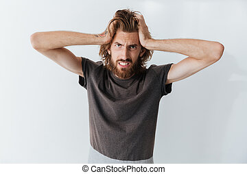 Caucasian angry man standing isolated over grey wall