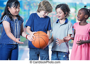 Caucasian, asian and afroamerican primary students playing baske