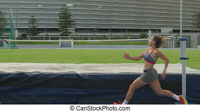Caucasian athlete doing high jump - Side view of a Caucasian...