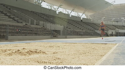 Caucasian athlete doing long jump - Low angle front view of ...