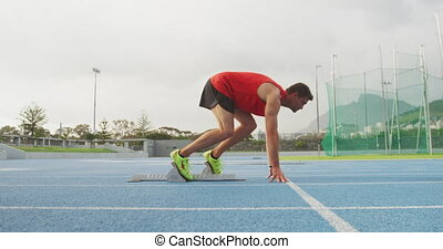 Caucasian athlete running in stadium - Side view of a ...
