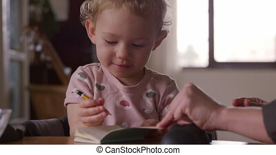 Front view of a Caucasian toddler enjoying family time at home, the mother sitting next to her baby, colouring together, slow motion