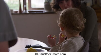 Caucasian baby eating at home - Side view of a Caucasian ...